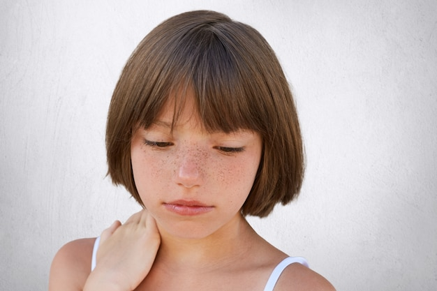 Close up of attractive little child with freckles and dark short hair keeping her hand on neck, looking seriously down, having thoughtful expression while posing on white concerete wall