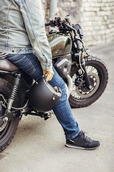 自転車に座ってヘルメットを手に持ってデニムの服と手袋を着用している魅力的な男性モデルを閉じます。