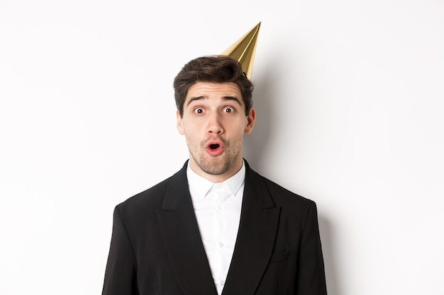 Primo piano di un uomo attraente con cappello da festa e abito alla moda, che sembra sorpreso, festeggia il nuovo anno, in piedi su sfondo bianco.