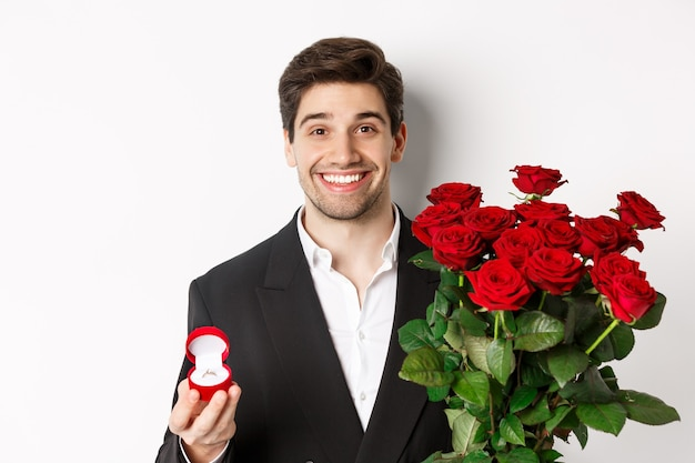 Close-up of attractive man in suit, holding bouquet of roses and engagement ring, making proposal, standing against white background