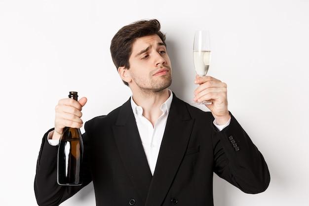Primo piano dell'uomo attraente in abito alla moda, degustazione di champagne, guardando il vetro, in piedi su sfondo bianco.