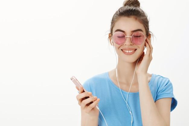 Primo piano della donna moderna attraente in occhiali da sole che ascolta la musica, godendo della canzone in auricolari, che tiene smartphone
