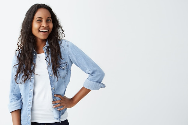 Chiuda su di posa di modello femminile sorridente dalla pelle scura sorridente astuta attraente isolata sulla parete bianca. sorridendo allegramente con i denti bella donna vestita con pelle scura e lunghi capelli ondulati