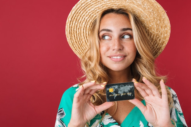 Close up of an attractive smiling young blonde woman wearing summer dress and straw hat standing isolated over pink wall, showing credit card