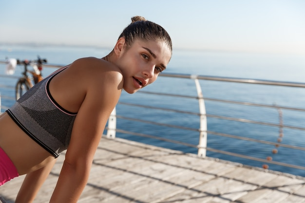 Close-up of attractive sportswoman taking a breath during workout