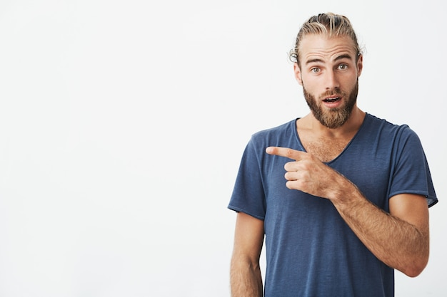Close up of attractive swedish guy with good hair and beard looking with surprised expression pointing at white wall. copy space.