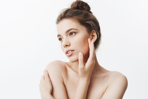 Close up of attractive tender young european woman with dark hair in bun hairstyle being naked looking aside with calm expression, touching face with hands posing for magazine photo shoot.