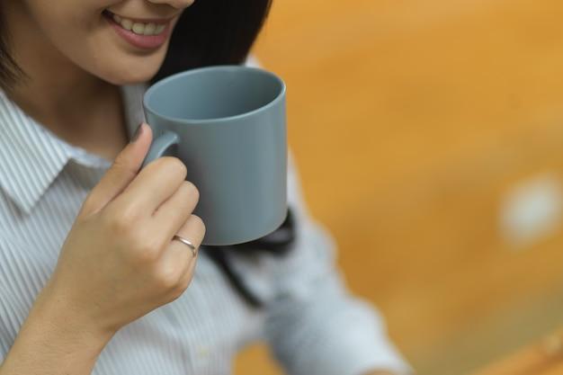 흐릿한 배경으로 커피를 마시는 매력적인 여성을 닫고, 사무실에서 휴식을 취하세요