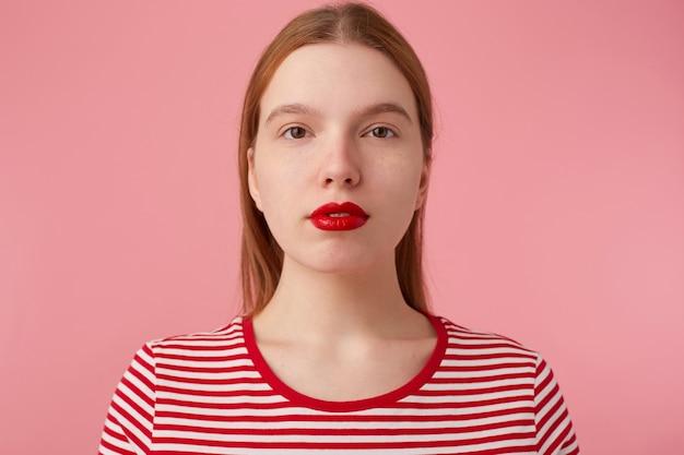 Primo piano di attraente giovane donna allo zenzero con labbra rad, indossa una maglietta a strisce rossa, guarda con un'espressione calma, si alza.