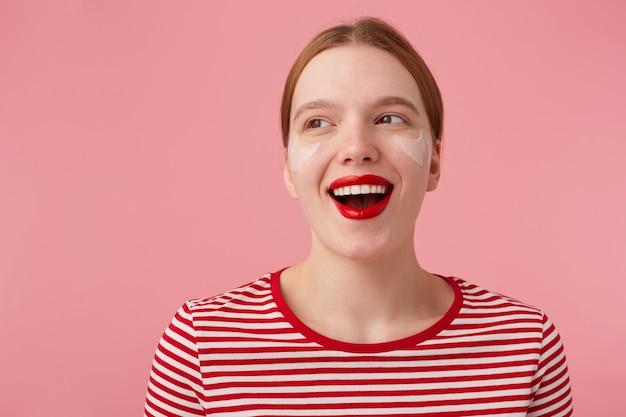 Primo piano di attraente giovane donna dai capelli rossi felice con labbra rosse e con macchie sotto gli occhi, indossa una maglietta a righe rosse, distoglie lo sguardo e ampiamente sorridente, si alza.