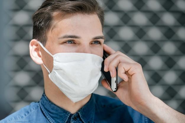 확대. 스마트 폰 이야기 보호 마스크에서 매력적인 젊은 남자. 도시의 코로나 바이러스