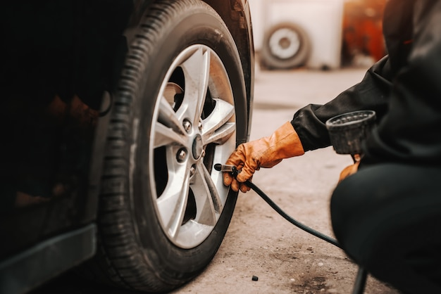 Close up of auto mechanic using tire pump on car tire in workshop.