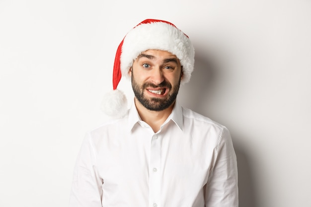 Close-up of awkward guy in santa hat apologizing, feeling uncomfortable, standing over white background. christmas concept.