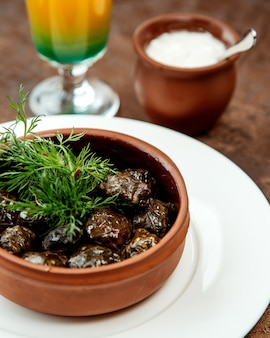 Close up of azerbaijani grape leaves dolma placed in pottery pan garnished with dill