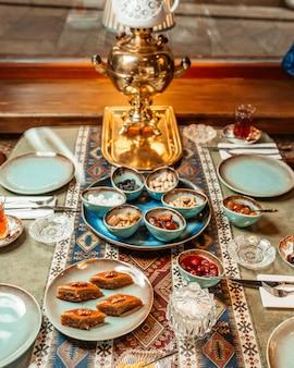 Close up azerbaijani tea setup with pakhlava samovar jams and nuts