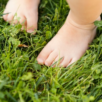 잔디에 아기 발을 닫습니다