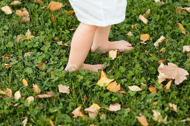 Крупным планом детские ножки в траве