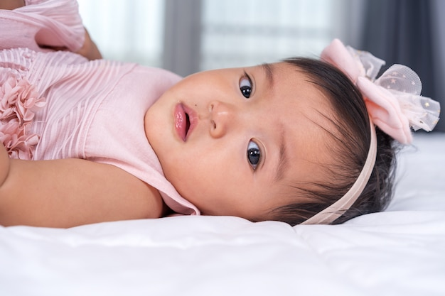 Close up baby in pink dress on bed