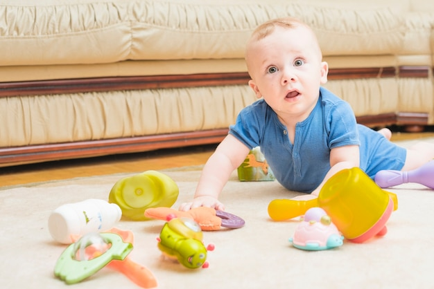 Close-up of baby playing with colorful toys on carpet