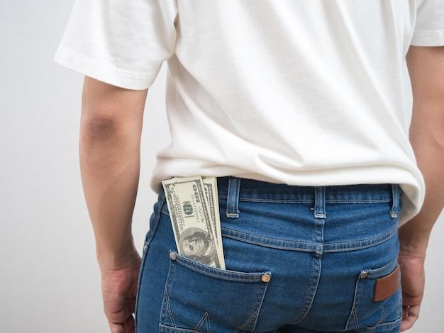 ズボンの男のお金のドルの後ろを閉じるジーンズポケットの肖像画白い背景