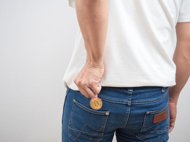 男の後ろを閉じてズボンのジーンズのポケットから金色のビットコインを拾う