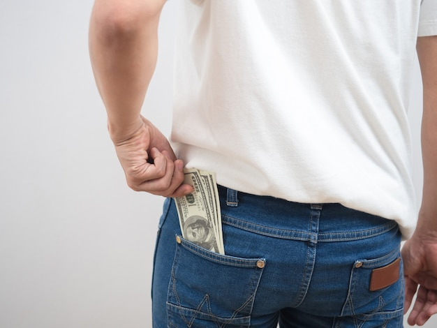 男の後ろをクローズアップズボンのジーンズのポケットからお金を拾う