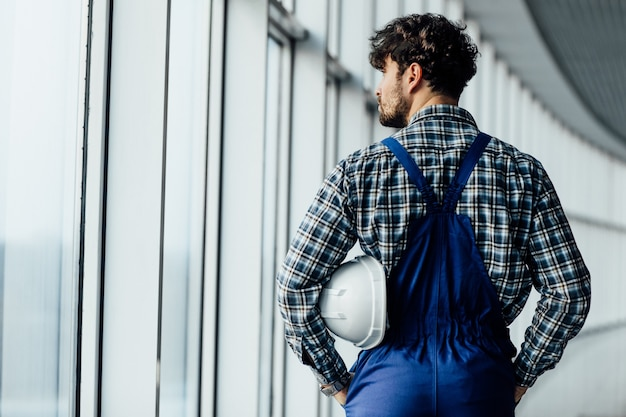 Close up back view of man construction worker holding helmet indoor