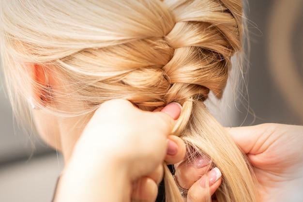 Крупным планом вид сзади женские руки, плетущие косичку молодой блондинке в салоне красоты