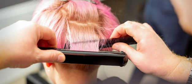 헤어 아이언으로 짧은 분홍색 머리카락을 곧게 펴는 미용사의 손을 다시 볼 수 있습니다.