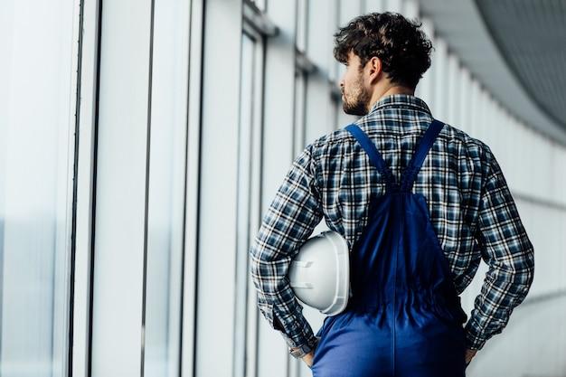 屋内でヘルメットを保持している男性建設労働者の背面図を閉じる
