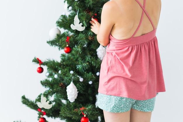 크리스마스 트리를 장식하는 여자의 클로즈업 다시보기. 휴일 및 축하 개념.