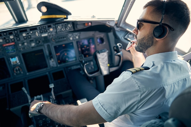 Close up back view portrait of handsome confident male pilot in sunglasses preparing for leaving airport