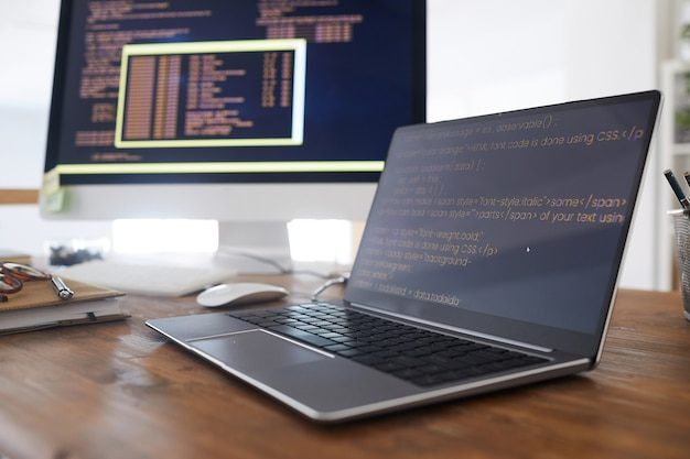 Close up background image of black and orange programming code on computer screen and laptop in contemporary office interior, copy space