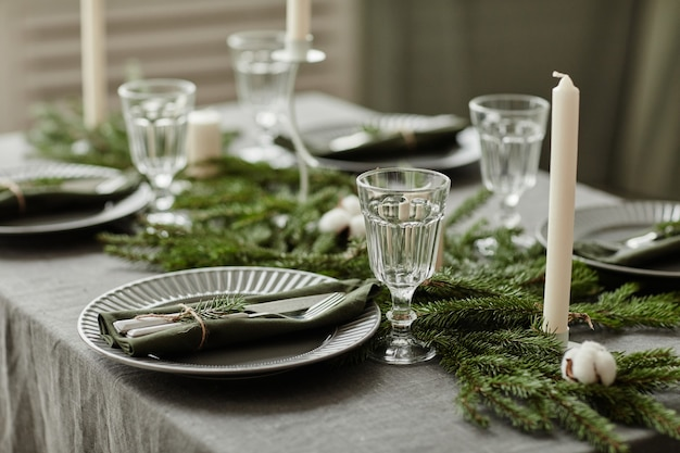Close up background image of elegant dining room setting for christmas with table decorated with fir...