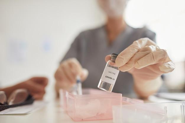 Крупным планом фоновое изображение руки врачей, держащей вакцину covid в центре вакцинации, копией пространства