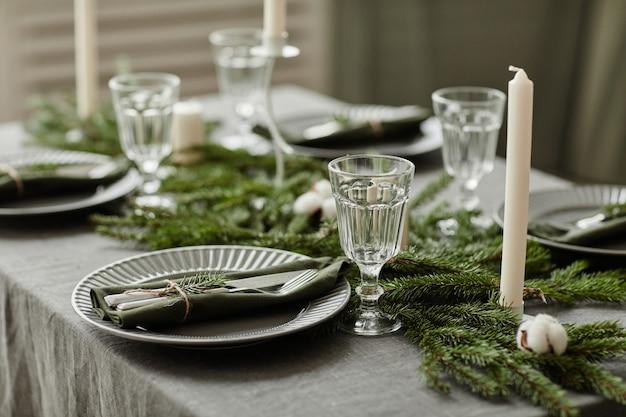 전나무로 장식된 테이블이 있는 크리스마스를 위한 우아한 식당 설정의 배경 이미지를 닫습니다...