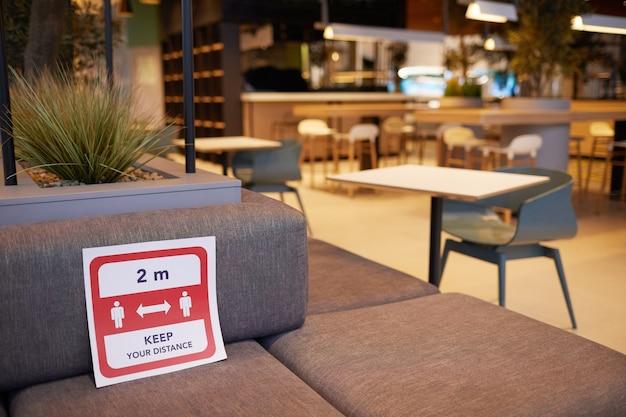 赤い社会的な距離のサイン、コピースペースでショッピングモールの空のフードコートのインテリアの背景画像を閉じる