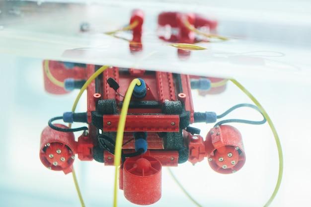 Крупным планом фоновое изображение красной роботизированной лодки с камерой в резервуаре для воды в лаборатории инженерии и робототехники, копией пространства