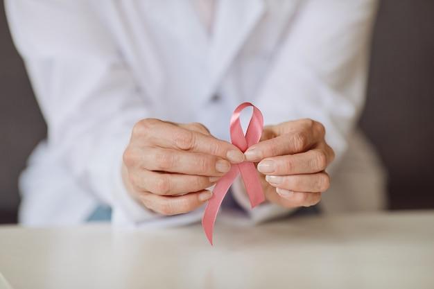 유방암 인식, 복사 공간의 상징으로 흰색 실험실 코트에 핑크 리본을 들고 인식 할 수없는 여성 의사의 배경 이미지를 닫습니다