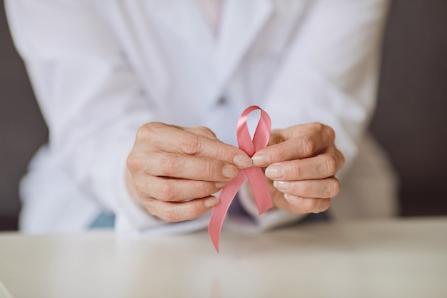 Close up background image of unrecognizable female doctor holding pink ribbon against white lab coat as symbol of breast cancer awareness, copy space