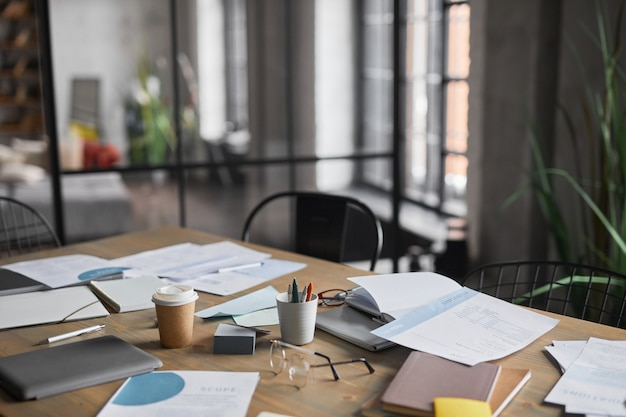 Close up background image of wooden table with documents scattered on after business meeting in office, copy space