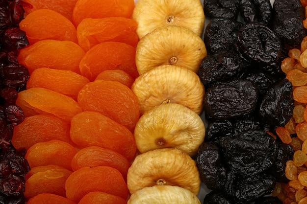 各種日干しフルーツ、レーズン、プラム、アプリコット、イチジク、高角度ビューの背景パターンを閉じる
