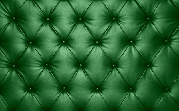 Close up background texture of dark green capitone genuine leather, retro chesterfield style soft tufted furniture upholstery with deep diamond pattern and buttons