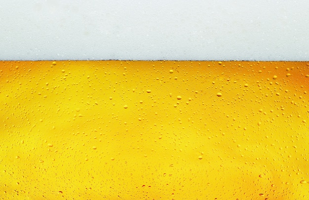 Close up background texture of lager beer with bubbles and froth in glass.