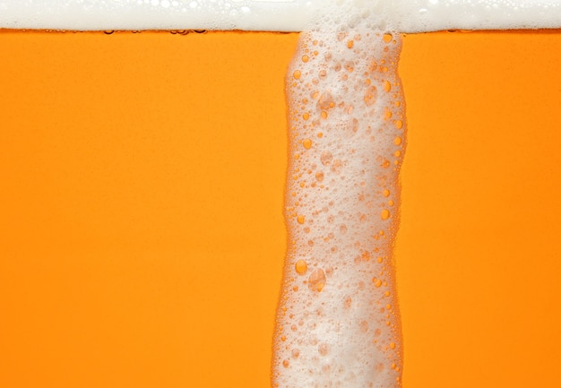 Close up background texture of lager beer with bubbles and froth, pouring in glass, low angle, side view