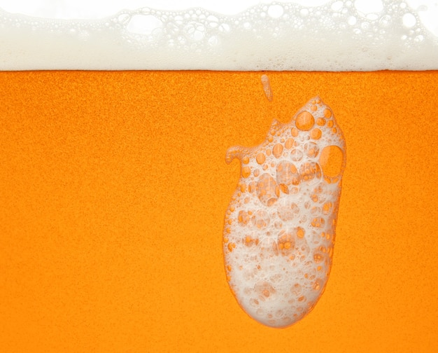 Close up background texture of lager beer with bubbles and froth