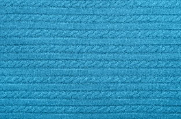 パステルブルーのケーブルニットウールジャージー生地のセーターの背景のテクスチャを行編みパターンでクローズアップ