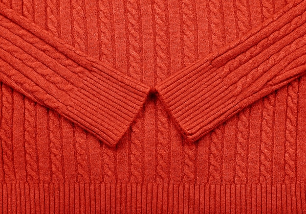 행 브레이드 패턴으로 빨간색 케이블 니트 울 저지 원단 스웨터의 배경 질감을 닫습니다