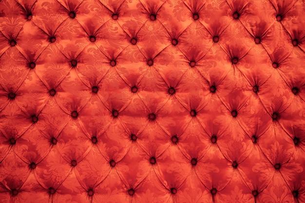 緋色の赤いcapitone本革、レトロなチェスターフィールドスタイルのソフトの背景の質感をクローズアップ