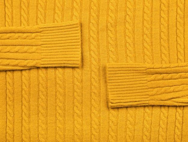 행 브레이드 패턴으로 따뜻한 노란색 케이블 니트 울 저지 원단 스웨터의 배경 질감을 닫습니다